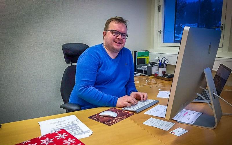 rektor redvald hjulstad sitter foran mac-skjermen på kontoret sitt og jobber