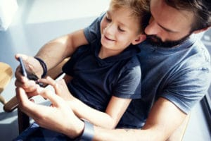 Far har sønn på fanget mens de ser på telefonen sammen