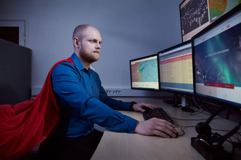 Børge fra IT hos Signal Bredbånd er ikledd rød kappe mens han jobber foran sine fem dataskjermer