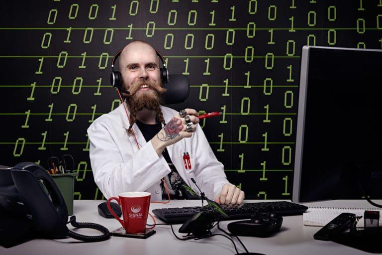 Chris fra Signal Bredbånd sitter foran en vegg av et binært tallsystem. Han har fletter i skjegget og snakker med kunder i hodetelefonene sine
