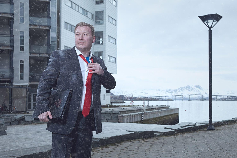Mats fra Signal Bredbånd er ikledd dress og står ute i snøværet i Bodø, på vei til kundemøte