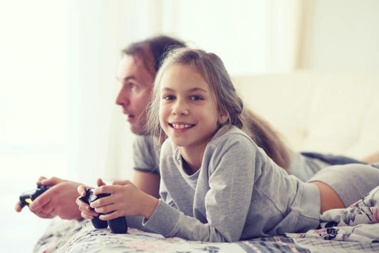 Jente ser inn i kameraet, glad og fornøyd, midt i en dataspillkamp med sin far, som er dypt konsentrert i bakgrunnen.