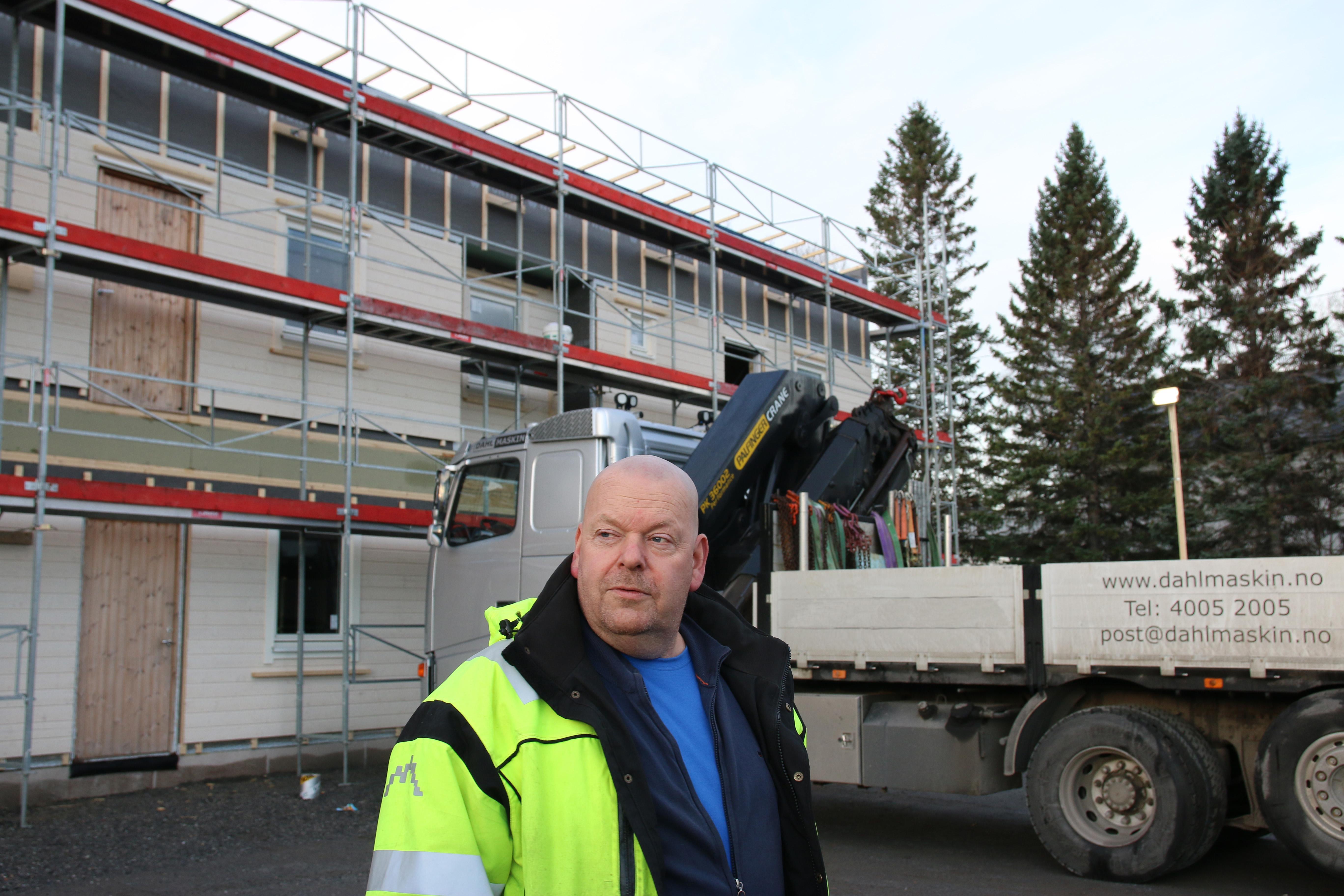 Mann i refleksjakke står fremfor lastebil merket med Dahl Maskin