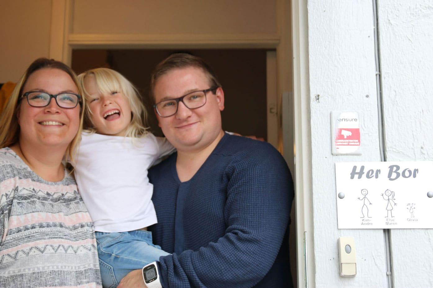 Liten jente holder rundt foreldrene sine mens de står i døråpningen til boligen sin