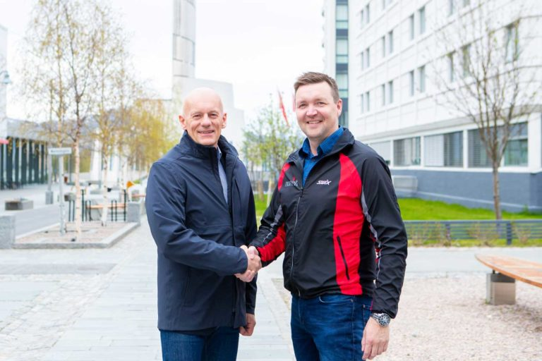 Adm direktør i Signal Bredbånd AS tar Roger Strømeng, daglig leder i Nornett AS i hånda etter å ha skrevet under på kjøpskontrakt