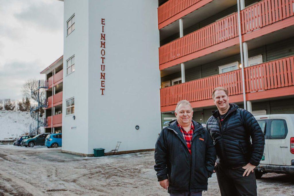 Fiberkunde og styreleder i Einmotunet Borettslag og salgssjef BRL fra Signal Bredbånd står fremfor bygget