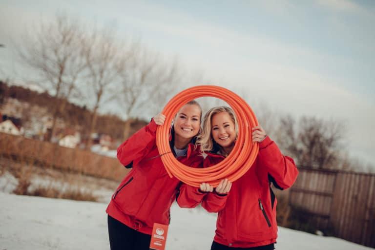 To rødkledde damer fra Signal Bredbånd ser gjennom en trommel av fiberkabel
