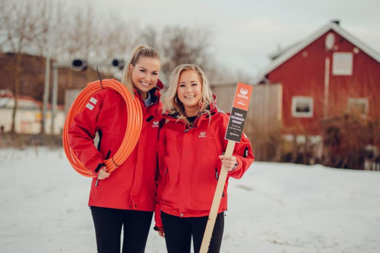 To damer fra Signal bredbånd i røde jakker holder fiberkabel og skilt foran hus om vinteren.