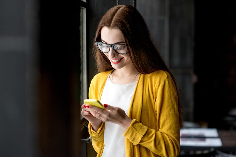 Kvinne i gul jakke og briller ser ned og surfer på internett på smartelefonen sin