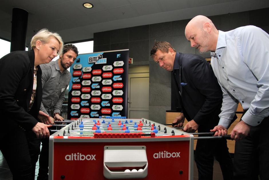 Komersielle ledere fra Norsk Toppfotball og Altibox smiler fremfor sin fornyede sponsortavle