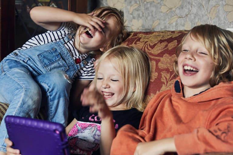 tre barn sitter og ler av en video på en ipad