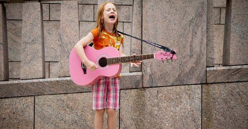 Liten jente med rosa gitar synger for full hals