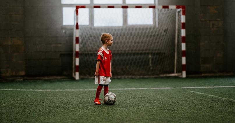 Liten gutt står i fotballdrakt med en fotball fremfor et fotballmål