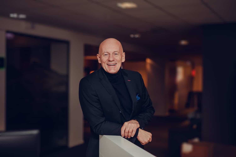 Administrerende direktør Ole-Johnny Johansen lener seg over en benk og smiler. Han gleder seg over kjøpet av fiberinfrastrukturen i Bodø