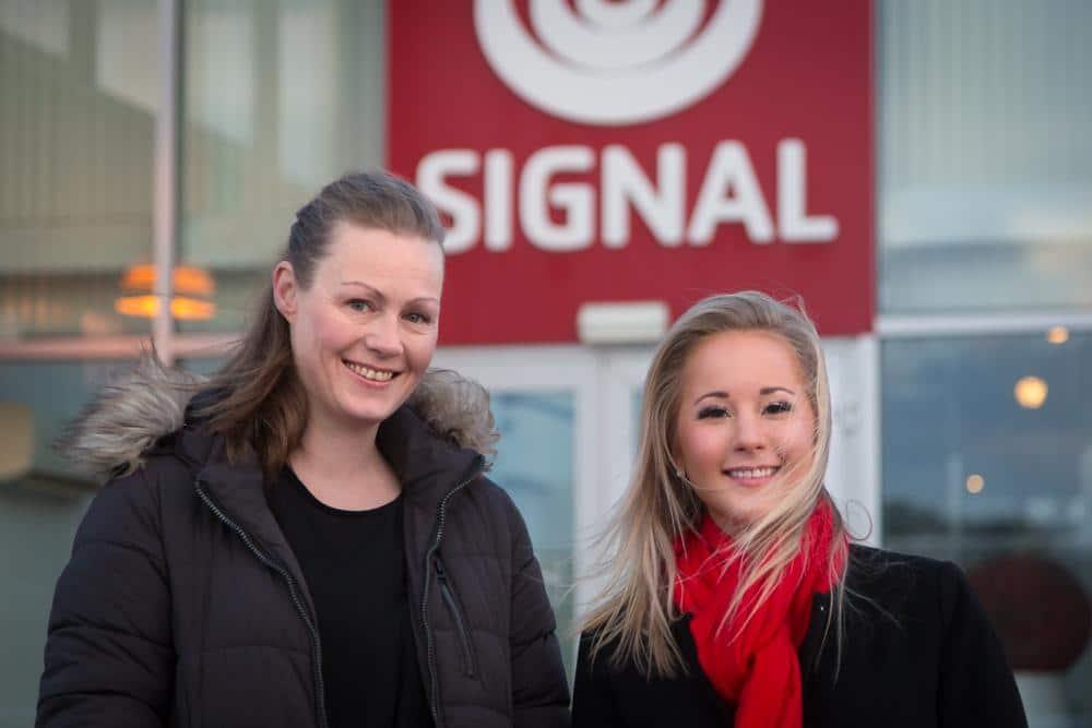 Økonomisjef Grethe Simonsen og leder for Markedsstøtte og Samfunnskontakt, Stine Værang står foran et rødt Signal-skilt.