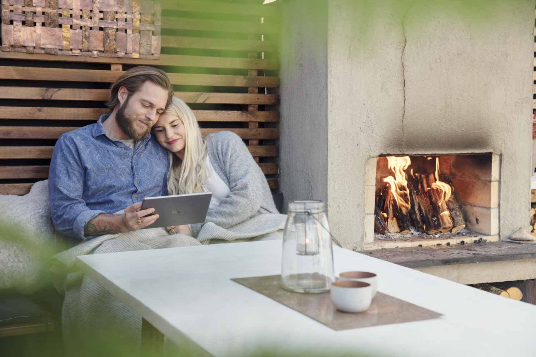 Jente sitter i armkroken til kjæresten sin og ser tv på ipad foran seg, ved siden av en utepeis.
