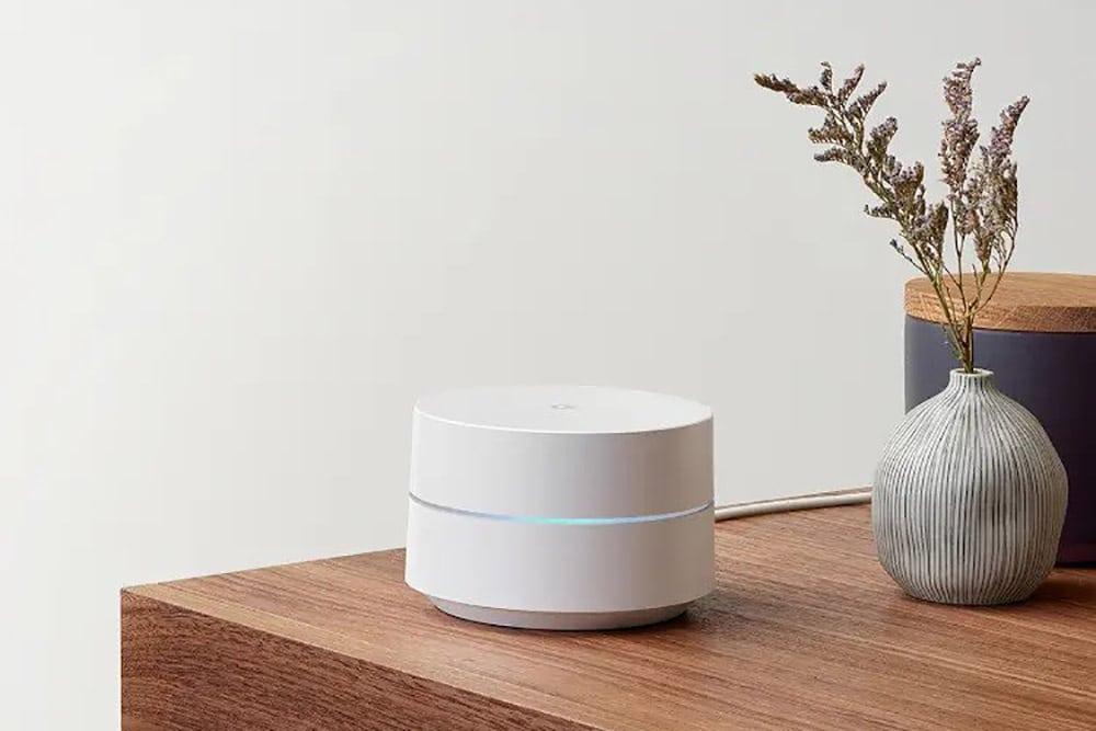 Google Wifi enhet står på et bord ved siden av en plante