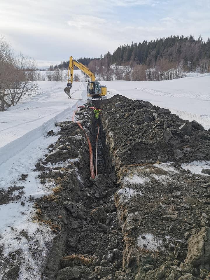 Gravemaskin graver opp en vinterkledd bakke for å legge fiber