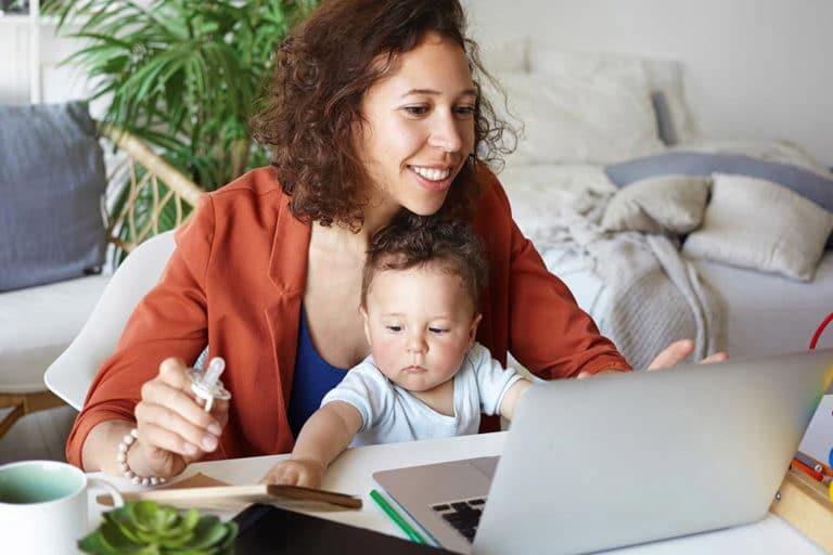 Mor og barn sitter på gulvet foran en sofa med laptop og leker på bordet