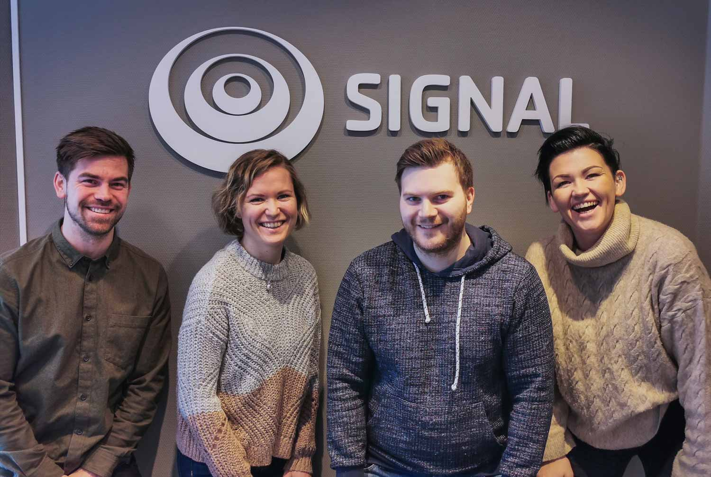 Fire ansatte fra kundesenteret i Signal Bredbånd i Alta står foran Signal-logoen på veggen