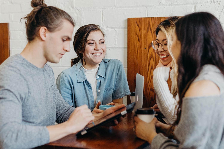 Kollegaer sitter rundt et lite bord på hjemmekontor og prater og ler sammen