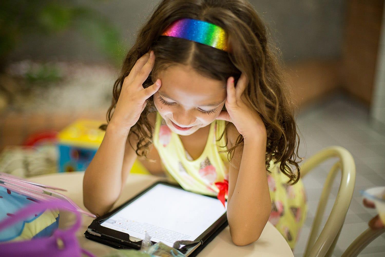 Jente med fargerikt hårbånd sitter med en ipad mellom hendene og smiler