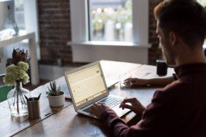 Ung mann surfer på nettet sammen med venn på en kafé