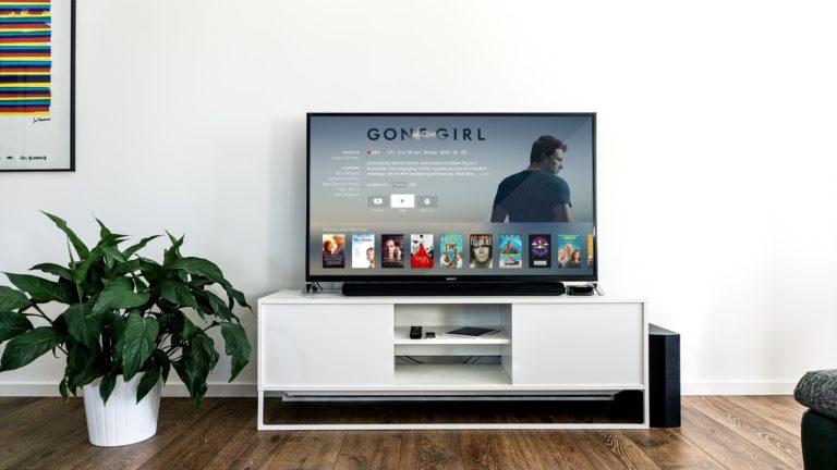 Flatskjerm på hvitt tv-bord viser filmutvalg på skjermen