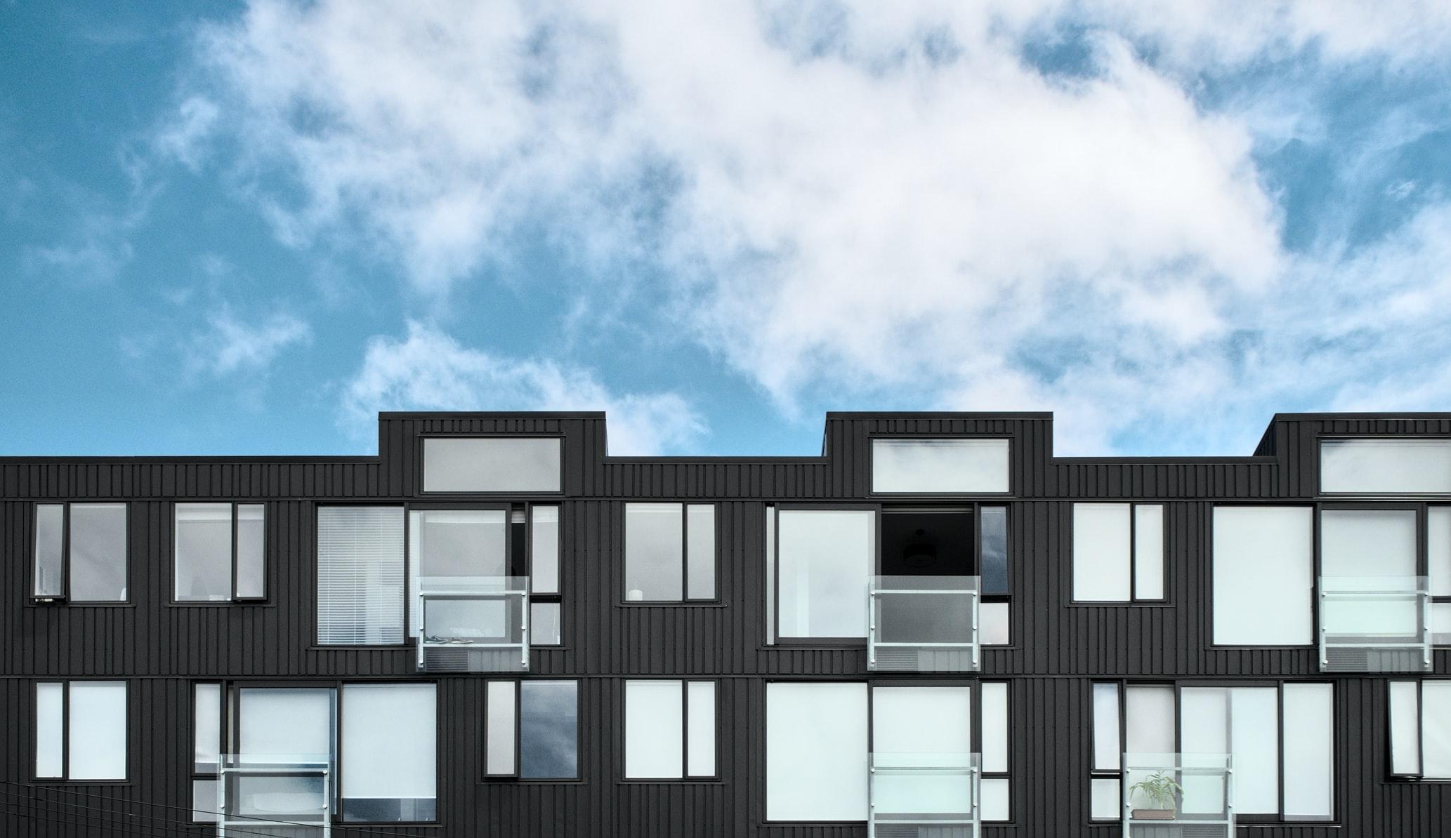 Moderne leiligheter med høye vinduer og arkitektisk byggutforming