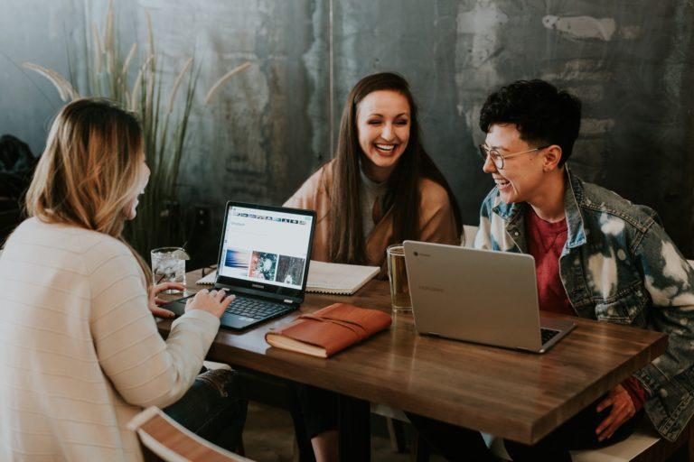 Tre studenter snakker og ler sammen rundt et lite bord på kafé