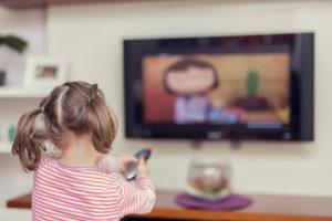 Liten jente med musefletter sitter med ryggen til og ser på barne-tv
