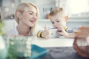 Mor og sønn videochatter ved kjøkkenbordet