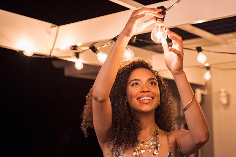 Jente smiler mens hun strekker seg opp mot lyslenke og fester en pære til lenken