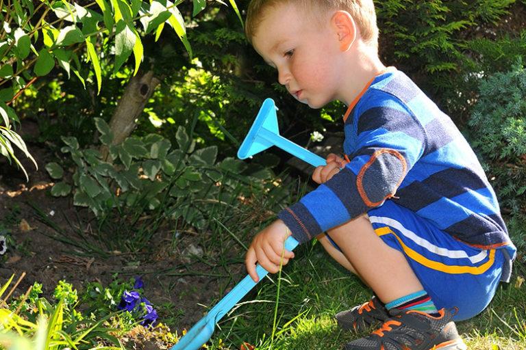 Liten gutt sitter på huk og leker ved en liten busk med hageredskap