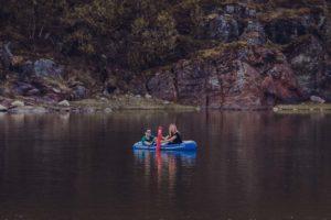 """Stine og Robin fra Signal Bredbånd ror i en gummibåt for å sjøsette sensorteknologien """"Badetassen"""" i vannet"""