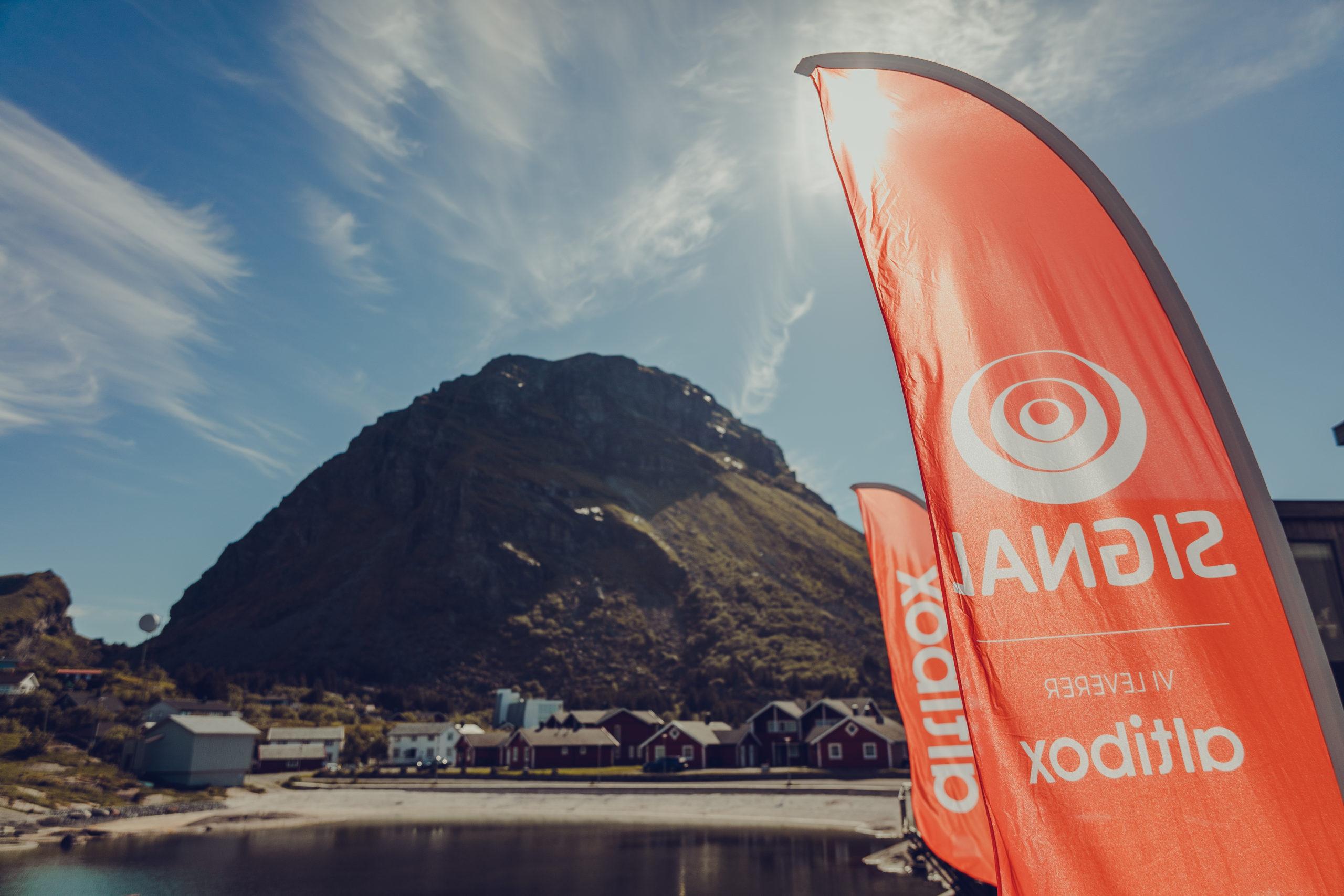 Signal Altibox beachflagg blåser i vinden med Lovundfjellet og Valplassen i bakgrunn