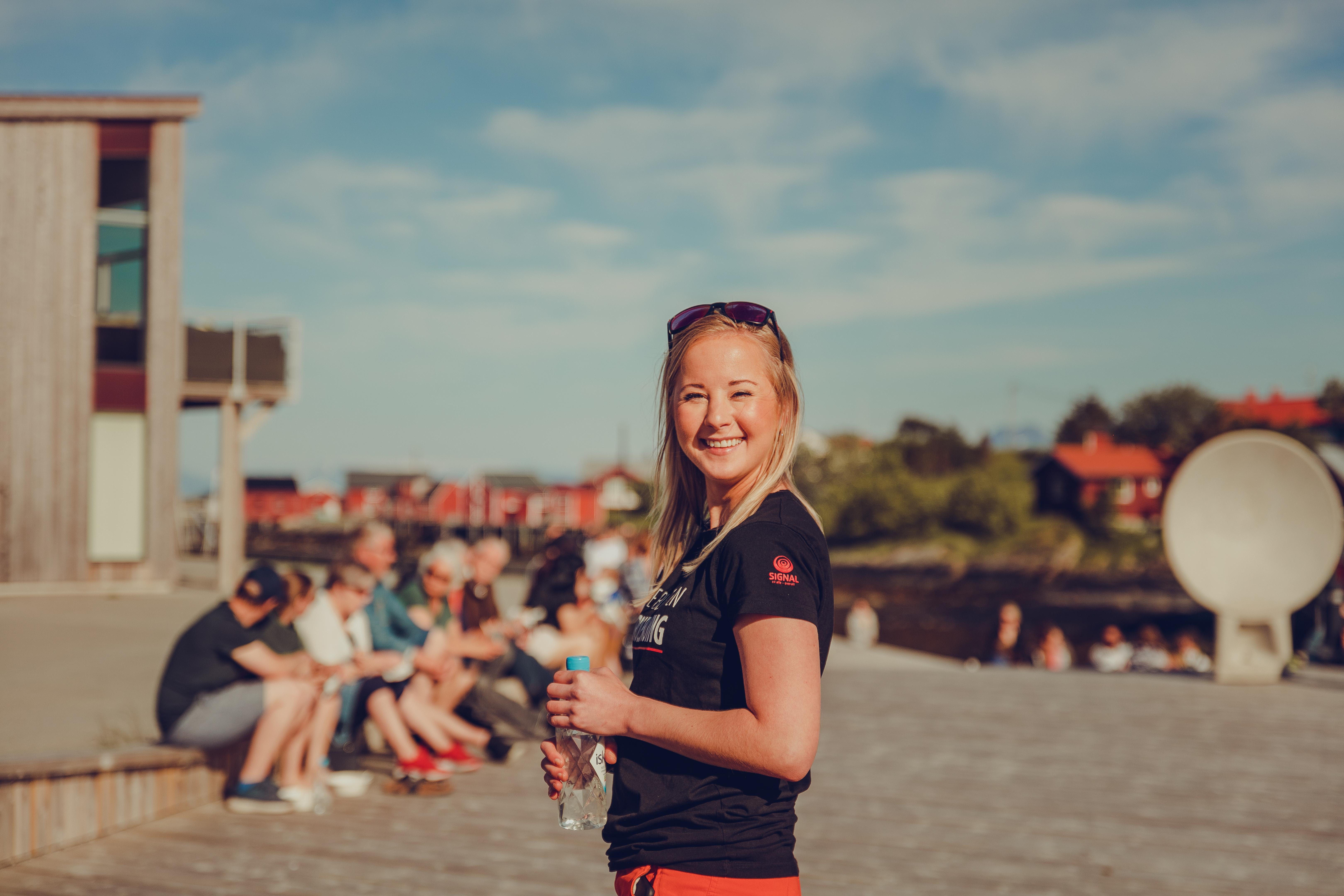 Stine Værang fra Marked i Signal står i kveldssola på Valplassen på Lovund med solbriller på hodet