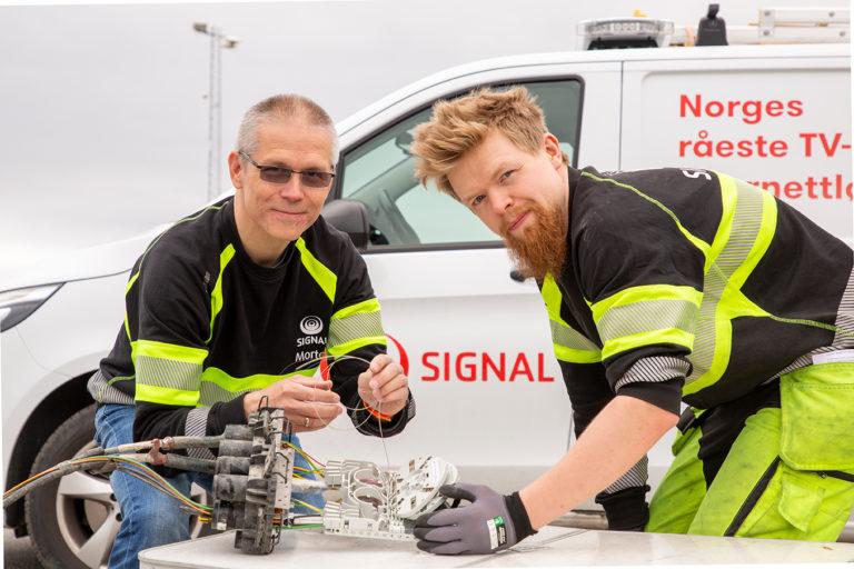 To montører fra Signal Bredband feilsøker på fiberboks fremfor en hvit varebil med rød logo på