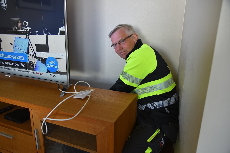 Montør i arbeidstøy sniker seg inntil veggen bak TV-bordet for å montere fiberkabelen til boksen