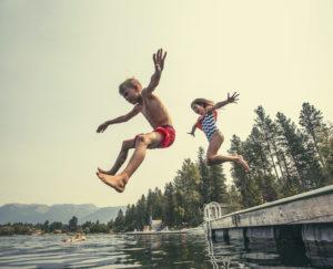 To barn tar sats og hopper fra en brygge og ned mot vannet