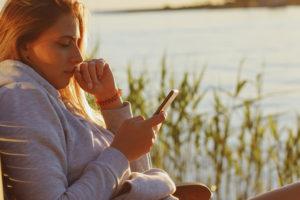 jente sitter i kveldsola og ser på mobilen sin