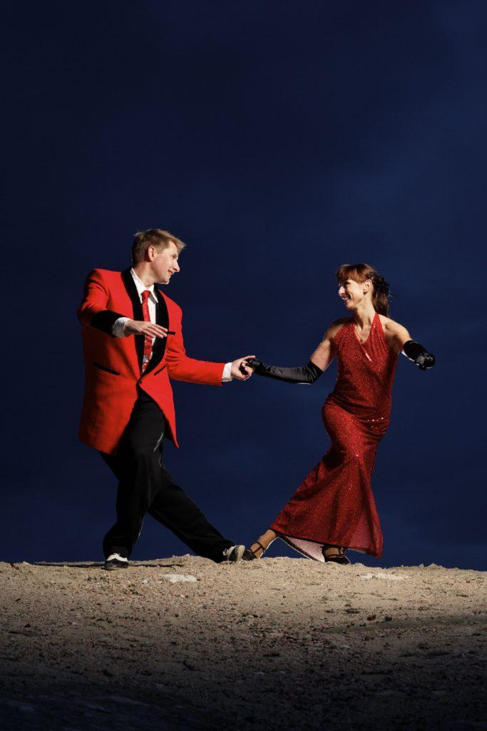 Par i rød dress og kjole danser boogie woogie mot mørk blå himmel