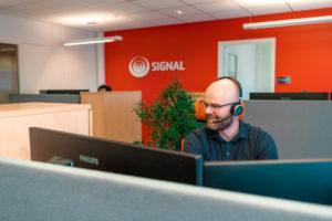 Kundesenterleder, Truls Are Ratkje sitter fremfor dataskjermer med headset på, og med rød vegg med signal logo i bakgrunnen
