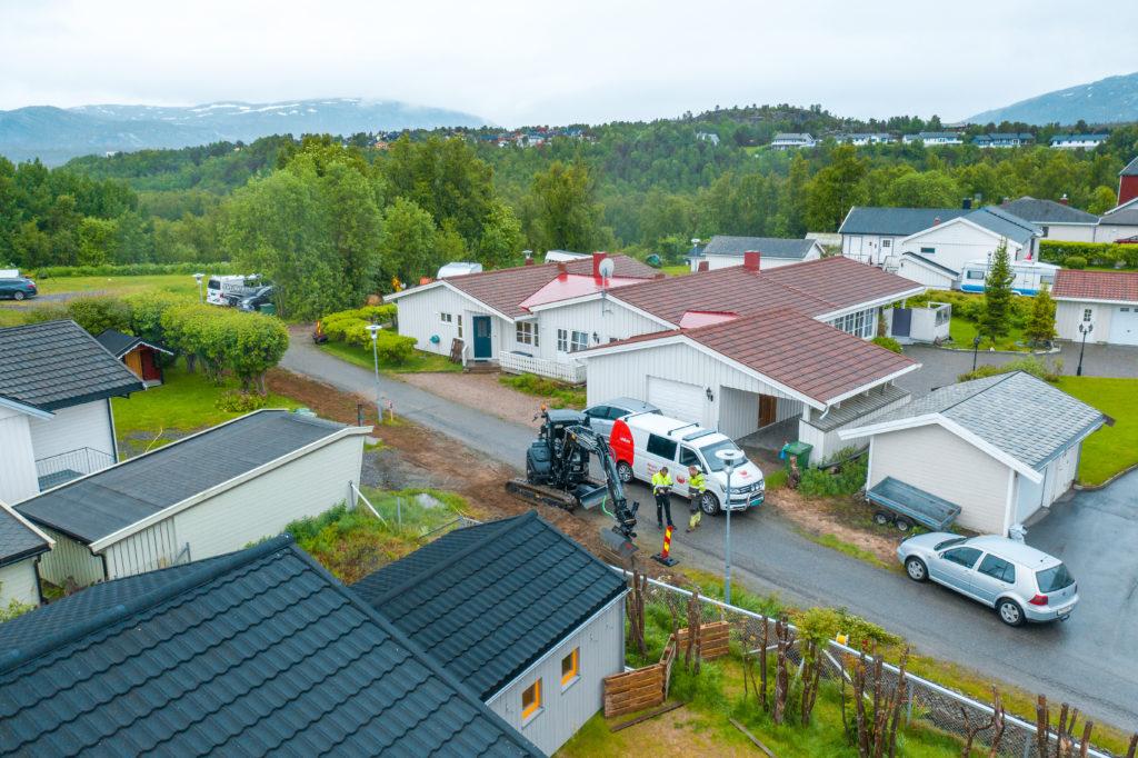 Boligområde i Alta bygges ut med ny fiber hvor en hvit transporter og en sort gravemaskin står parkert