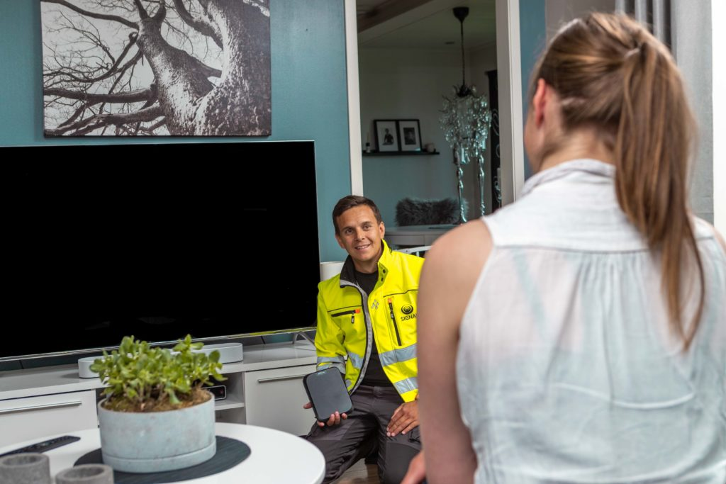 Montør fra Signal i gul arbeidsjakke viser en kvinnelig kunde med hestehale en Altibox boks