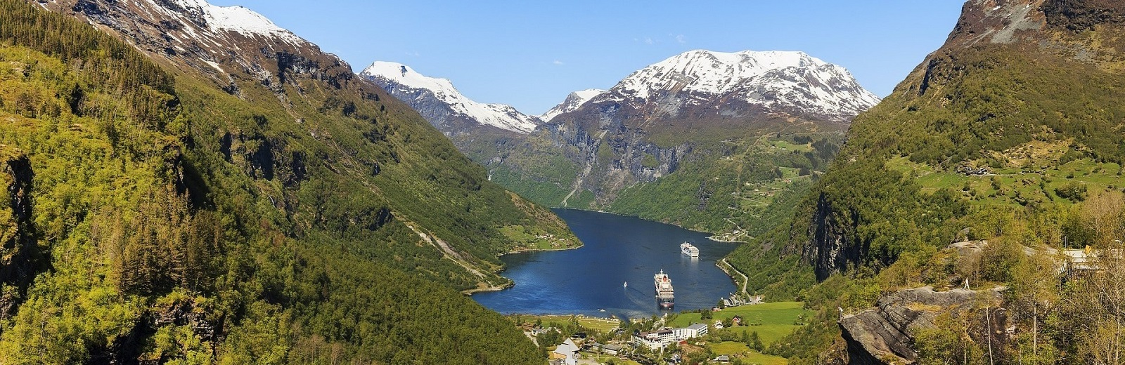 grønne fjell omringer fjorden i Geiranger hvor hurtigruten legger inn til kai