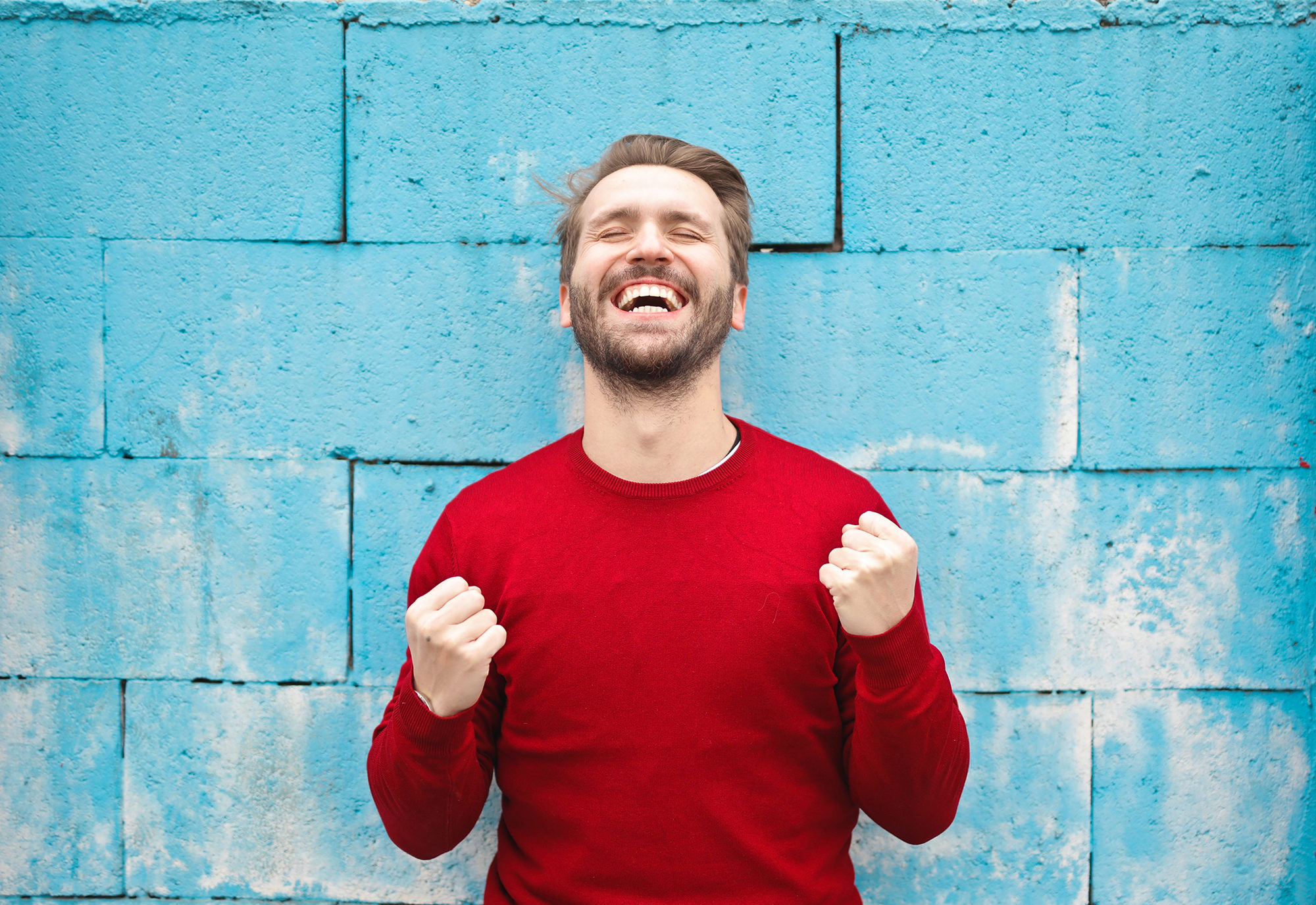 Glad mann i rød genser smiler bredt