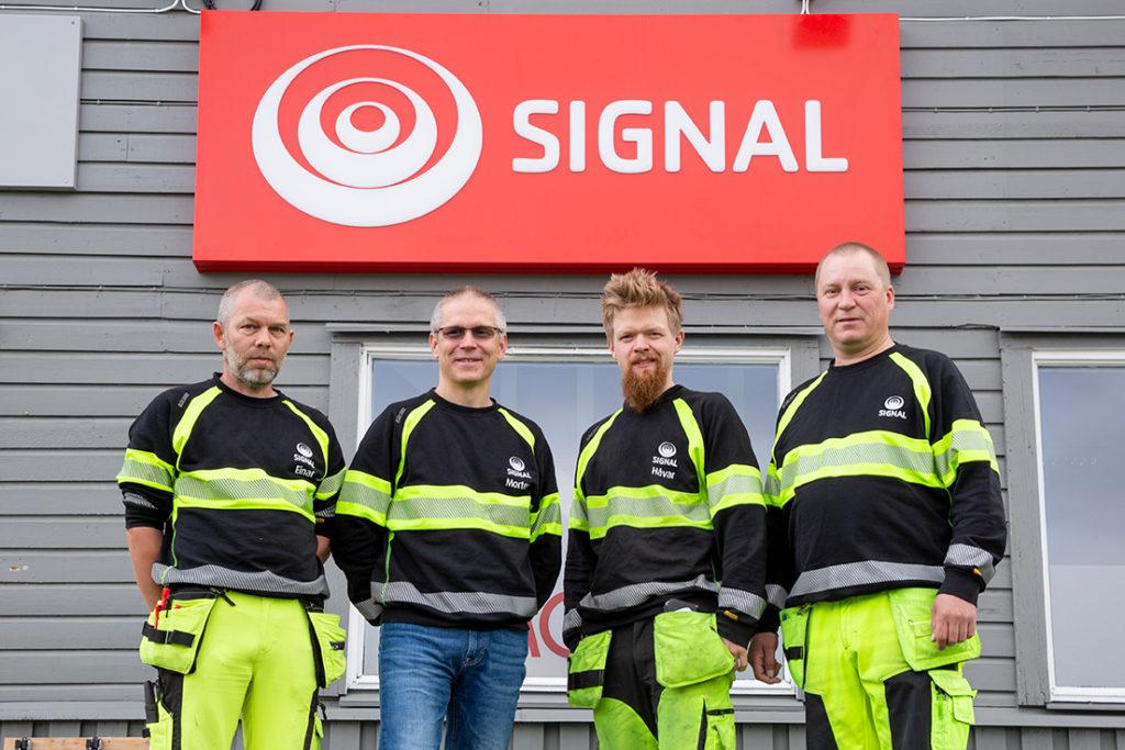 Fire menn kledd i svart og gult arbeidstøy står foran en grå vegg med rødt Signal-skilt