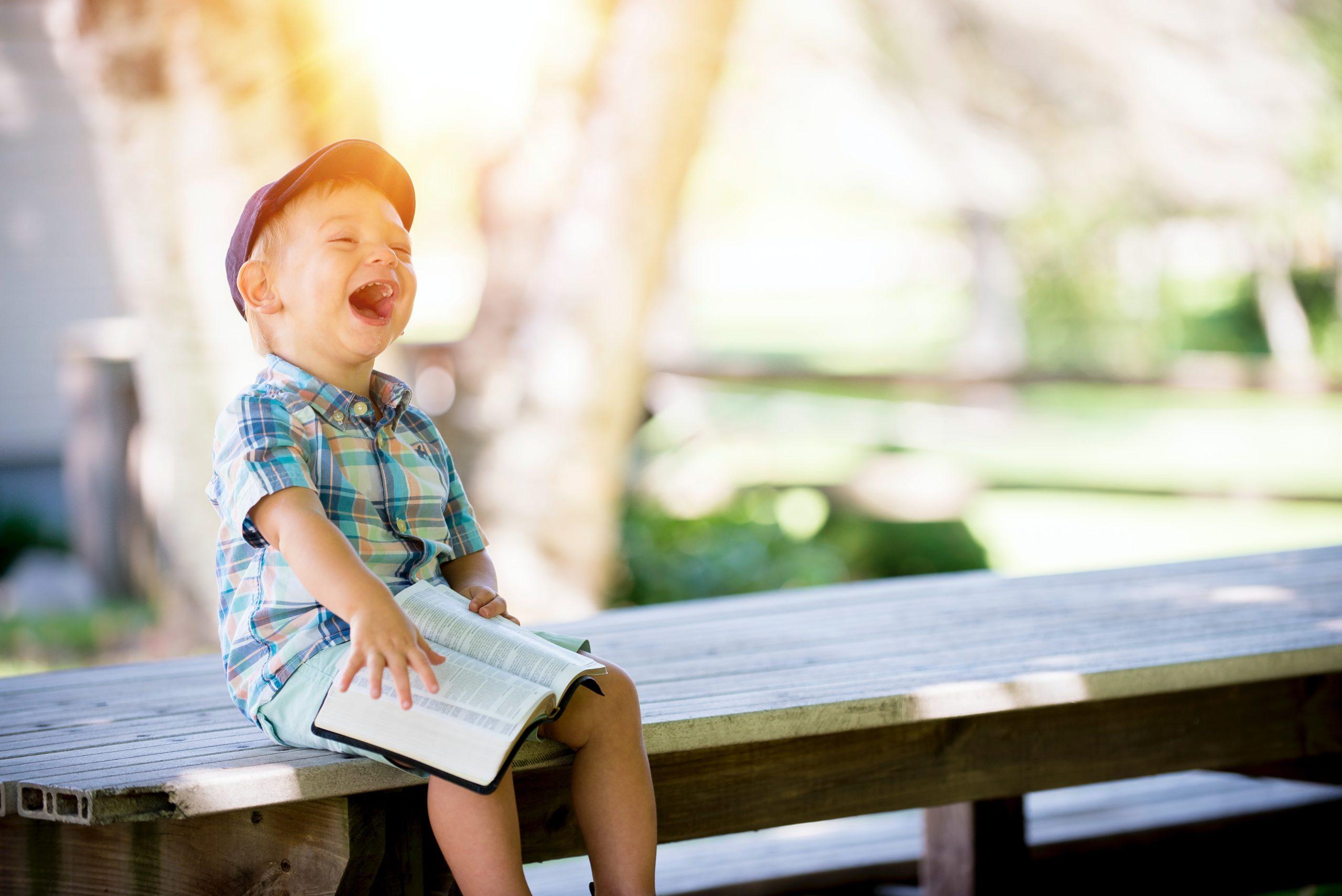 Liten gutt med sixpence sitter på en benk i parken og leser og ler av en bok
