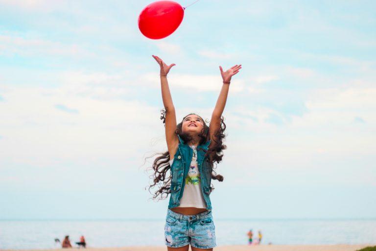Liten jente kaster en rød ballong opp i lufta